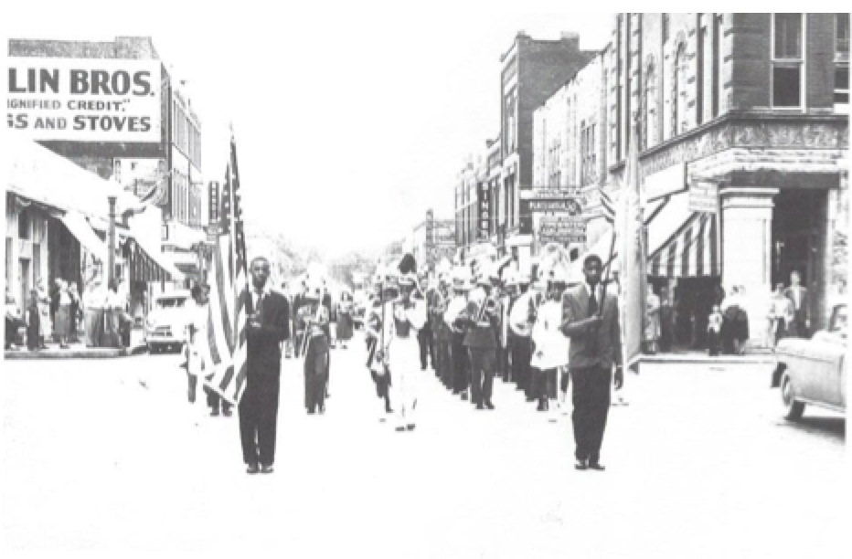 This is the highly acclaimed marching black band of Lincoln-Hubbard High School on the Northside of Sedalia before the days of integration. (probably in the 1950's) They are on Ohio Street, heading north in downtown Sedalia. On the right in the picture is the Safeway Grocery Store on the corner. Further down is the Singer Sewing Machine Store.. On the left, barely visible is McLaughlin Bros. Furniture Store and Funeral Chapel. None of those businesses are presently in operation.